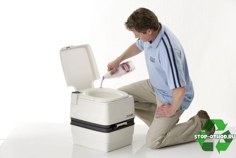 Мужчина заливает жидкость в биотуалет